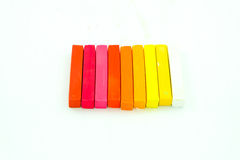 Chalk colored. A row of chalk colored on worm-tone color in white background Royalty Free Stock Photography