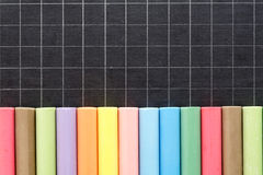 Chalk of colour lined up on slate Stock Photography