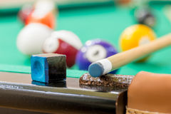 Chalk and cue on the edge of the table of billiard Stock Images