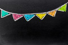 Chalk drawing as colorful party flag on black board background