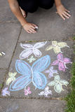 Chalk drawing of butterflies on sidewalk. Pavement with a butterfly chalkdrawing and hands of a child stock image