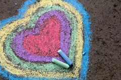 Chalk drawing: colorful hearts on asphalt. Copy space royalty free stock photography