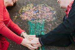 Chalk drawing. Couple hands, chalk drawing in the form of a bouquet royalty free stock images