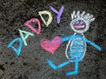 Chalk drawing: Cute father portrait and word DADDY. Chalk drawing on asphalt: Cute father portrait and word DADDY royalty free stock image