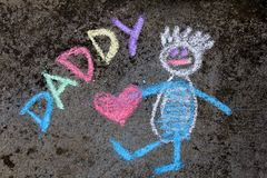 Chalk drawing: Cute father portrait and word DADDY. Chalk drawing on asphalt: Cute father portrait and word DADDY royalty free stock photography