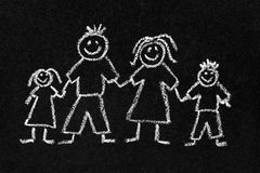 Chalk drawing of a family. Children's chalk drawing on a blackboard of a happy family with mum, dad, son and daughter stock photos