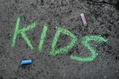 Chalk drawing: Green word KIDS. Colorful chalk drawing on asphalt: Green word KIDS royalty free stock images
