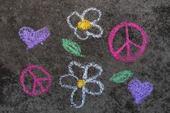 Chalk drawing: Pink peace symbol and beautiful flowers. Colorful chalk drawing on sidewalk: Pink peace symbol and beautiful flowers stock photography