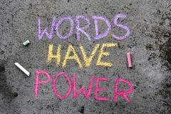 Chalk drawing: text WORDS HAVE POWER. Colorful chalk drawing on asphalt: text WORDS HAVE POWER stock photography