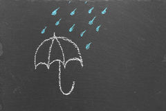 Chalk drawing of an umbrella and rain drops on slate Royalty Free Stock Photo