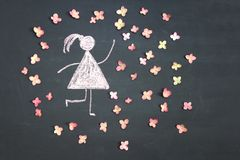 Chalk drawing woman icon surrounded by live pink flowers on chal. Kboard or blackboard. Women`s day, feminism, girl power concept stock photography