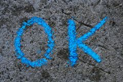 Chalk drawing : word OK. Colorful chalk drawing on asphalt: word OK stock photo