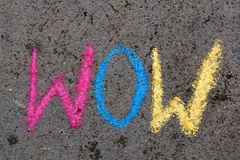 Chalk drawing: word WOW. Colorful chalk drawing on asphalt: word WOW stock photo