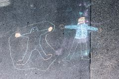 Chalk drawings on the street made by young children. Children`s chalk drawings on the street made by young children in their free time stock photo