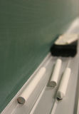 Chalk and Eraser. Closeup by chalkboard Royalty Free Stock Photo