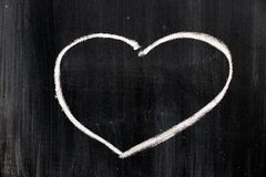 Chalk hand drawing as heart shape on black board