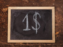 Chalk handwritten dollar sign on blackboard on wooden background Stock Photography