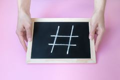 Chalk hashtag sign on blackboard held by female hands stock photos