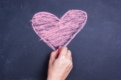 Chalk heart drawing. On a blackboard royalty free stock images