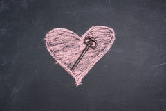 Chalk heart drawing and key. On a blackboard stock photos