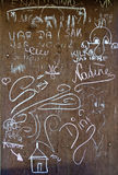 Chalk inscriptions and drawings on a rusty iron wall Royalty Free Stock Image