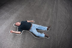 Chalk line and man. A man dead in the street outlined with chalk by crime scene investigators Stock Photography