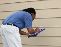 Chalk Marking Hail Damage To Siding. An insurance adjuster marks hail damage dings with white chalk and records his findings for a homeowner storm damage claim royalty free stock photo