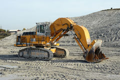 Chalk mine with excavator in front Royalty Free Stock Image