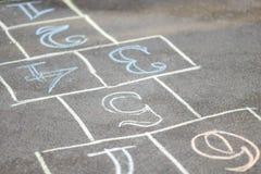Chalk-painted hopscotch on asphalt Stock Photos