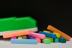 Chalk pastels and green blackboard eraser Royalty Free Stock Photos
