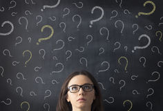Chalk question marks above businesswoman at blackboard Stock Images