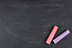 Chalk resting on a blank chalkboard background Royalty Free Stock Photos