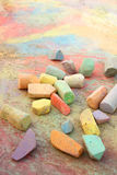 Chalk Scattered on Sidewalk. A collection of rainbow colored sidewalk chalk is scattered on the pavement outside, on top of a bright, colorful drawing stock photography