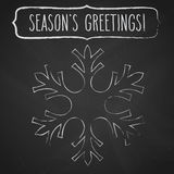Chalk Snowflake and Season's greetings. Chalk snowflake and a frame with hand written season's greetings over black chalkboard Stock Image