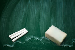 Chalk and sponge on a green chalkboard Royalty Free Stock Photos