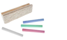 Chalk sticks with eraser. Several chalk sticks next to a board eraser. Isolated on White. White space at the right. Focus at the front royalty free stock photo