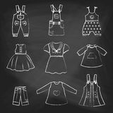 CHALK style icons. Set of cute dresses for the little girl. Collection of clothing in a linear style for the child. Stock Images
