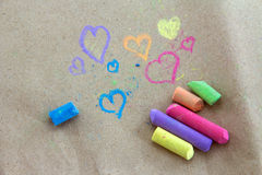 Less chalk in a variety of colors arranged on a Brown paper. Royalty Free Stock Photography