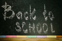 Chalk with words back to school. An inscription written in chalk back to school on an old blackboard Stock Image