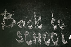 Chalk with words back to school. An inscription written in chalk back to school on an old blackboard Stock Photos