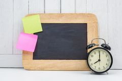 Chalkboard, Alarm clock and blank sticky note, post note or post Royalty Free Stock Images