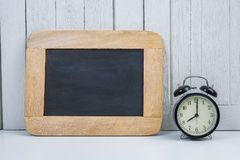 Chalkboard and Alarm clock on Office desk white wooden vintage b Stock Photos