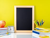 Chalkboard, apple and school supplies on white table by the yell. Ow wall. Side view, empty space for text. Back to school concept Stock Photo
