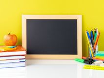 Chalkboard, apple and school supplies on white table by the yell. Ow wall. Side view, empty space for text. Back to school concept Royalty Free Stock Image