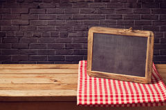 Chalkboard background with red checked tablecloth over black brick wall. Chalkboard background with red checked tablecloth Royalty Free Stock Image