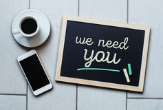 Chalkboard or Blackboard concept saying - We need you. With coffee and mobile phone. Business, Personal, Education, Effective, Management concept Stock Images