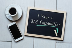 Chalkboard or Blackboard concept saying - 1 Year = 365 Possibili. Ties - with coffee and mobile phone. Business, Education, Effective, Inspiration, Personal Stock Photo