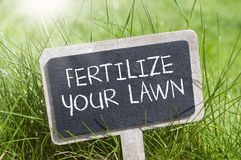 Chalkboard in the grass with fertilize your lawn. Chalkboard blackboard in the grass with fertilize your lawn stock images