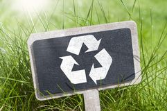 Chalkboard in the grass with recycling logo royalty free stock images