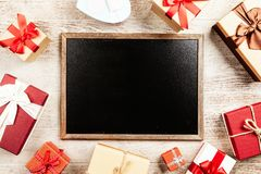 Chalkboard With Brown Wooden Frame Surrounded by Red Gift Boxes stock image